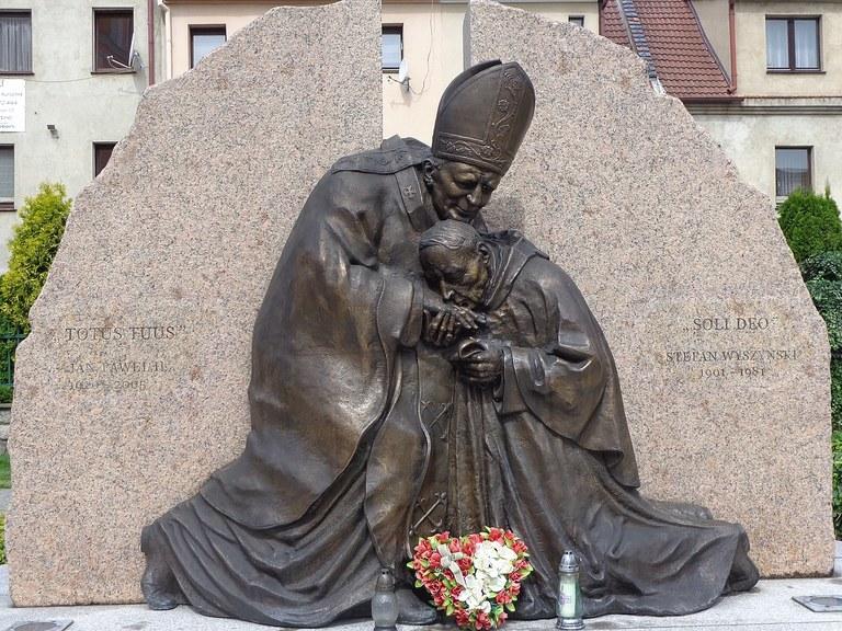1280px-Pomnik_Jana_Pawła_II_i_Stefana_Wyszyńskiego,_Plac_Farny_Prudnik.jpg